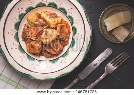 Traditional Italian Tortellini With Tomato Sauce, Mozzarella Cheese And Basil On Rustic Plate