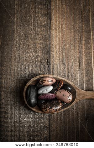 Colorful Raw Beans And Wooden Spoon On Dark Background