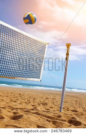 Bright beach scene with a net and volley ball at sunset