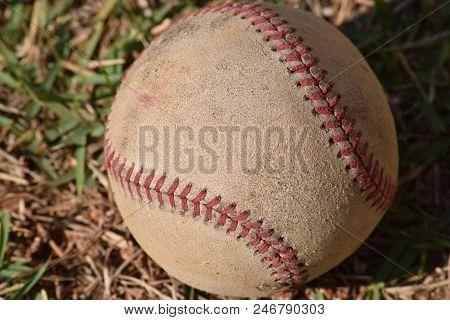 Nostalgic Baseball In The Grass On A Baseball Field