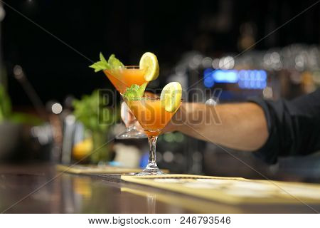 The Barman Gives A Cocktail To The Client Of The Hotel Bar. Fresh Cocktail With Orange. Alcoholic, N