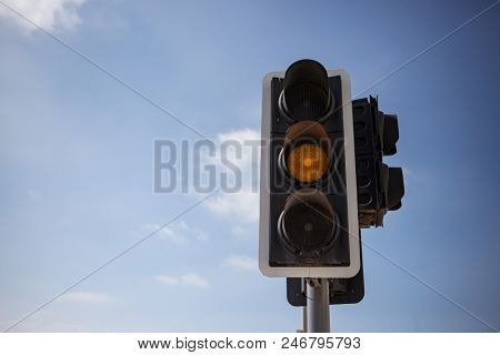 Yellow, orange color traffic light. Blue sky with few clouds background. Close up under view, space for text.