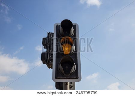 Yellow, orange color traffic light isolated. Blue sky with few clouds background. Close up under view.