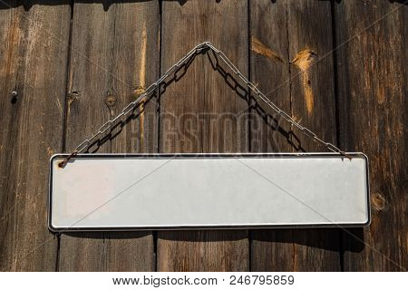 Wooden brown door with a white empty banner label hanging from metallic rusty chain in front of it. Closeup, space for text.