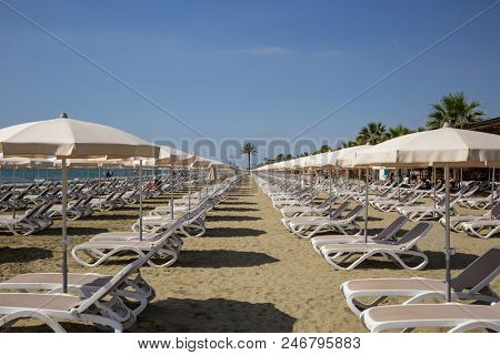 Mackenzie sandy beach at Larnaca, Cyprus. Sun loungers and umbrellas next to sea. Blue sky backdrop, closeup view.