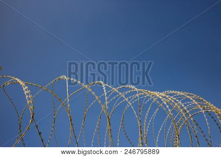 Wire circle mesh metal fence, sharp with razors, barbed, provides security and warning of danger. Blue sky backdrop, closeup.
