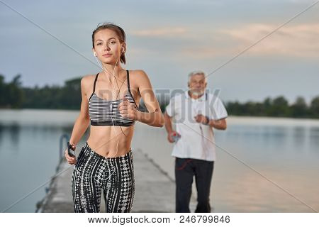 Sporty Girl With Fit Figure Running Near Lake In Evening. Senior Man Running Behind. Outdoor Activit