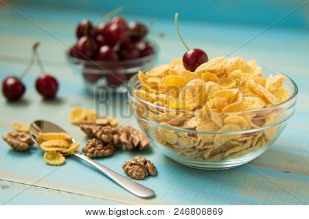 Tasty Cornflakes Wit Walnut And Cherry In Glass Bowl On Blue Background. Corn Flakes,