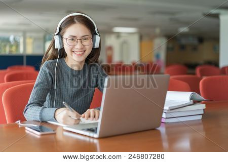 Beautiful Smiling Female Student Using Online Education Service. Young Woman Looking In Laptop Displ