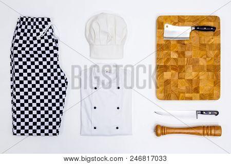 A flat lay arrangement of Chef whites uniform and equipment.