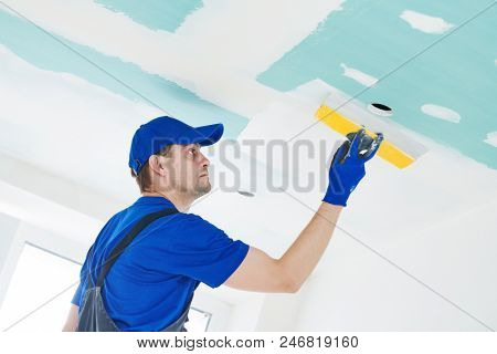 refurbishment. Plasterer spackling a gypsum plasterboard ceiling with putty poster