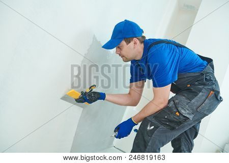 refurbishment. Worker spackling a wall with putty poster