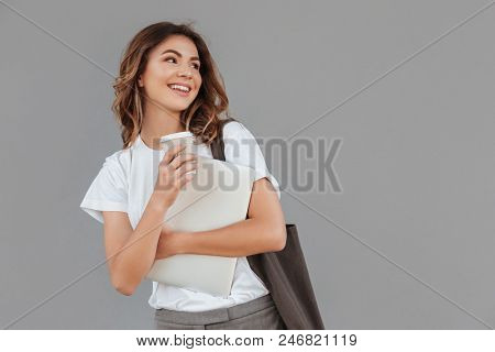 Image of attractive brunette woman 20s smiling and looking aside at copyspace while standing against gray wall isolated with silver laptop and takeaway coffee in hands