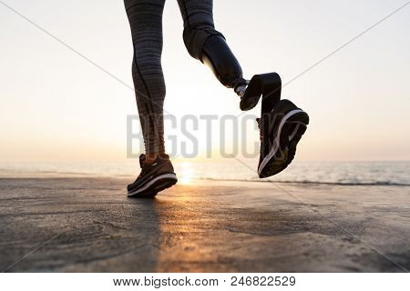 Close up of disabled woman with prosthetic leg running outdoor at the beach