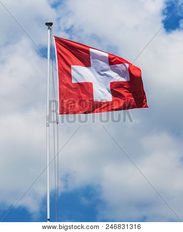 Flag Of Switzerland Against Cloudy Sky On The Windy Day.