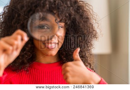 Curious african american woman looking through magnifying glass happy with big smile doing ok sign, thumb up with fingers, excellent sign