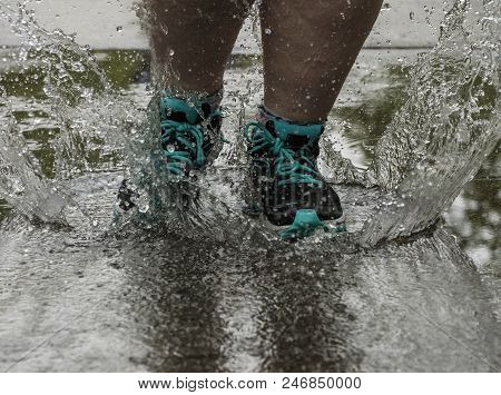 Feet Splashing In A Puddle Of Water
