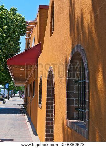 Orange Stucco Storefront In And Sidewalk In Bemidji Minnesota On A Sunny Day