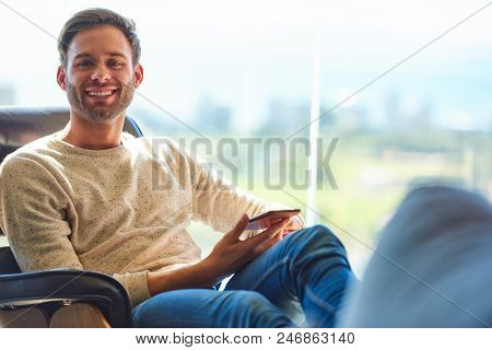 Caucasian Man Sitting On A Modern Couch Next To Large Glass Windows With A Stunning View Behind Him