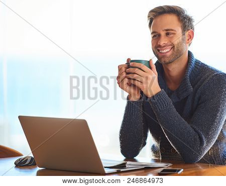 Handsome Young Caucasian Man, Happily Smiling While Holding His Coffee Mug For Warmth In The Morning