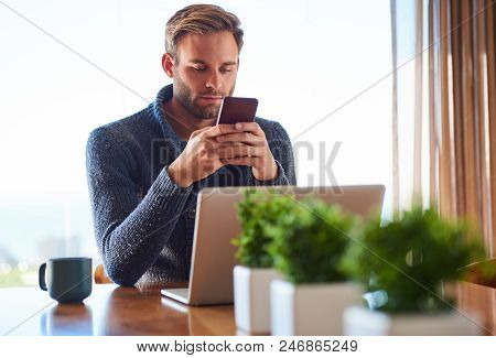 Handsome Young Man Texting On His Phone While Sitting At His Dining Table In The Comfort Of His Own