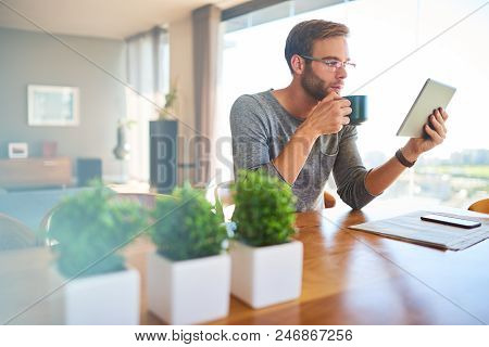 Attractive European Architect Busy Enjoying His Morning Cup Of Coffee While Looking At His Latest Pr
