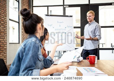 Businessman Present Marketing Plan To Team With Attractive Smile. People Working At Office Place Tog