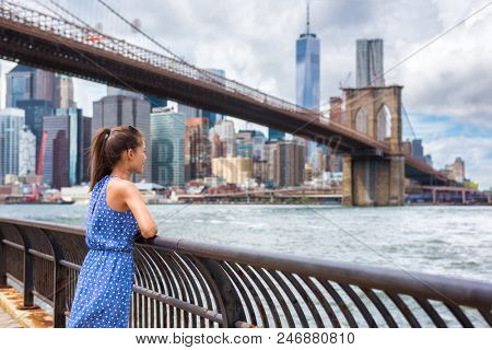 New York city NYC summer travel tourist woman enjoying view of Manhattan skyline from Brooklyn park living a happy lifestyle walking during USA vacation. Female Asian tourist in her 20s. poster
