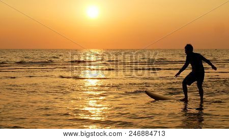 Silhouette Of Happy Surf Man Surfing With Long Surf Boards At Sunset On Tropical Beach. Surfer On Th