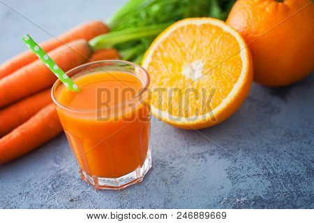 carrot and orange fresh juice on grey background - food and drink
