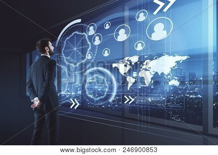 Businessman With Creative Glowing Digital Business Interface Standing In Modern Office Interior With