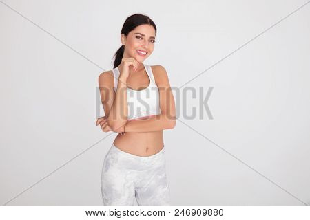 sexy and smiling gym girl posing while holding chin and standing on light grey background, portrait picture