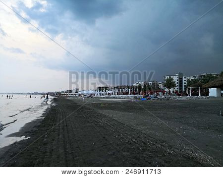 Storm At The Beach. Landscape With Beach, Sea And Hotels During Storm. Dark Clouds Over The Beach An