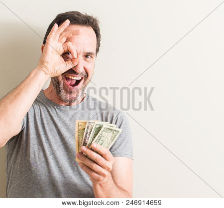 Senior man holding dollar money with happy face smiling doing ok sign with hand on eye looking through fingers