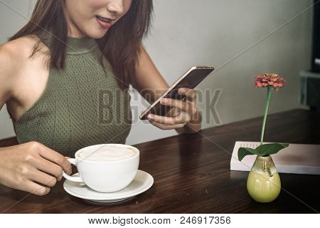 Young Woman Drinking Coffee And Using Her Phone At The Coffee Shop