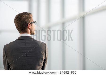 rear view.businessman standing near the office window