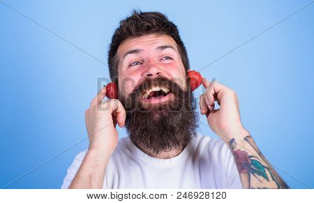Summer Hit Concept. Man Bearded Hipster Red Ripe Strawberry Ears As Headphones. Summer Top Radio Cha