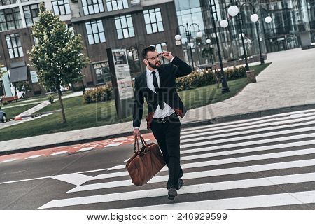 Confident Businessman. Full Length Of Young Man In Full Suit Crossing The Street While Walking Outdo
