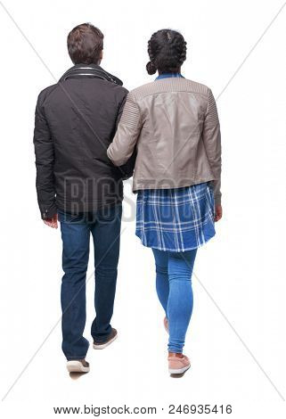Back view of interracial going couple. walking friendly girl and guy holding hands. Rear view people collection. backside view of person. Isolated over white. A couple in warm clothes on a stroll tog
