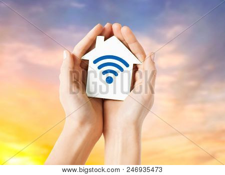 people, internet connection, security, alarm and technology concept - close up of hands holding house with radio or wifi wave signal icon over evening sky background