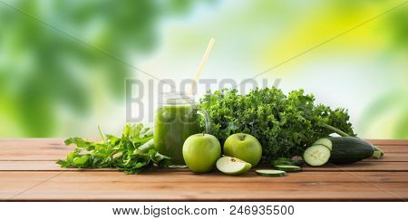 healthy eating, food, dieting and vegetarian concept - glass jug or mug with green juice, fruits and vegetables on wooden table over green natural background