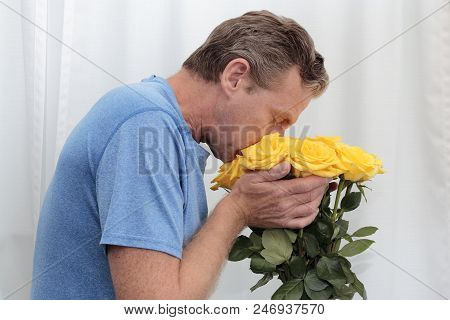 Mature Man With His Face In A Yellow Roses Bunch. Yellow Roses Being Held, Smelled By An Older Man.