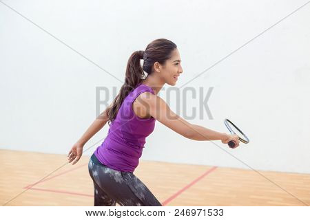 Side view of a young squash player holding the racket while standing with bent knees during game indoors on a professional court