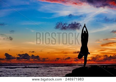 Sunset Meditation Silhouette. Active Woman Stand In Yoga Pose On Beach Rock To Keep Fit And Health.