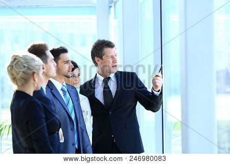 group of business people looking out the window,standing in the lobby of the office.
