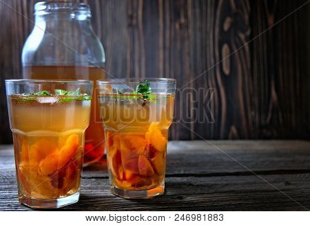 Fresh Homemade Peach Sweet Tea With Mint On Wooden Table. With Copyspace.