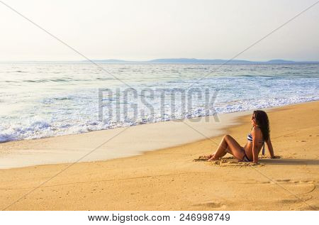 Single girl sitting in the golden sand by the sea shore in a summer day