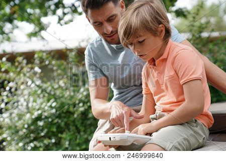 Daddy watching kid playing with video game console poster