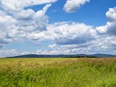Beautiful Cumulus cloudscape with a June meadow and Bulgarian Fore-Balkan mountain hills poster