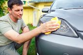 Wiping car- Young man cleaning car with microfiber cloth, car detailing in the house yard poster